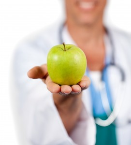 Close-up of a doctor presenting a green apple